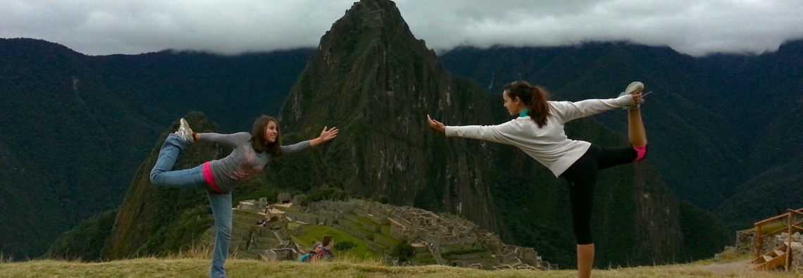 Gianna and Melissa demonstrate a Dancer's Pose at the top of Peru's Machu Picchu